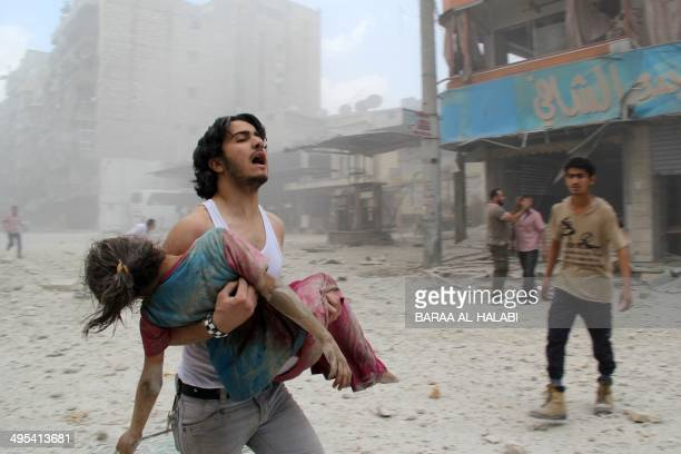 A man carries a young girl who was injured in a reported barrelbomb attack by government forces on June 3 2014 in Kallaseh district in the northern...