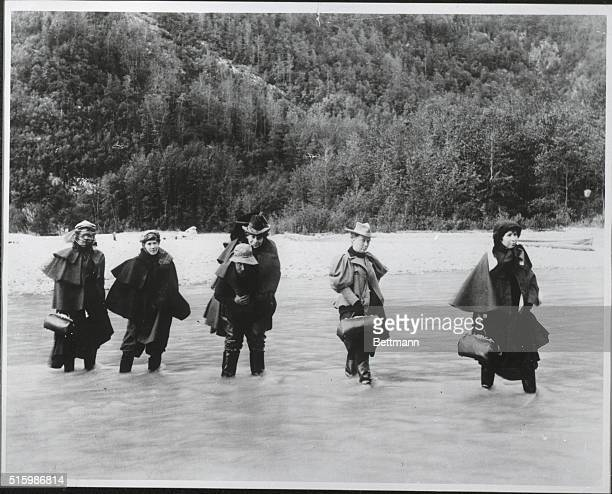 Man carries an actress across an Alaskan river while others must ford it to get to a gold mine.