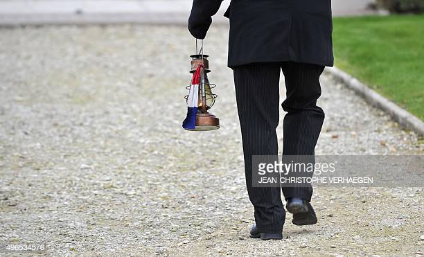 A man carries an 'eternal flame' during a dedication ceremony for seven unknown French WWI soldiers on November 10 2015 in Verdun eastern France at...