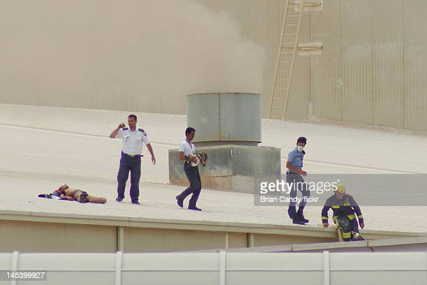 Man carries an injured child across a roof as emergency sevices seek to rescue people from a fire at the Villaggio mall on May 28, 2012 in Doha,...