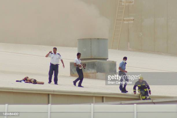 A man carries an injured child across a roof as emergency sevices seek to rescue people from a fire at the Villaggio mall on May 28 2012 in Doha...