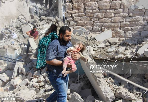 A man carries an injured child after Assad regime's airstrikes hit the town of Khan Shaykhun in Idlib in Syria on October 6 2017 At least 8 people...