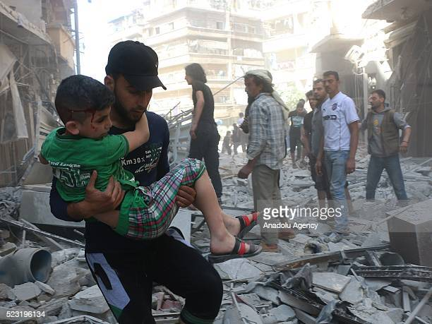 A man carries an injured child as the civil defense workers and civilians evacuate the wounded people and dead bodies pulled from the debris after...
