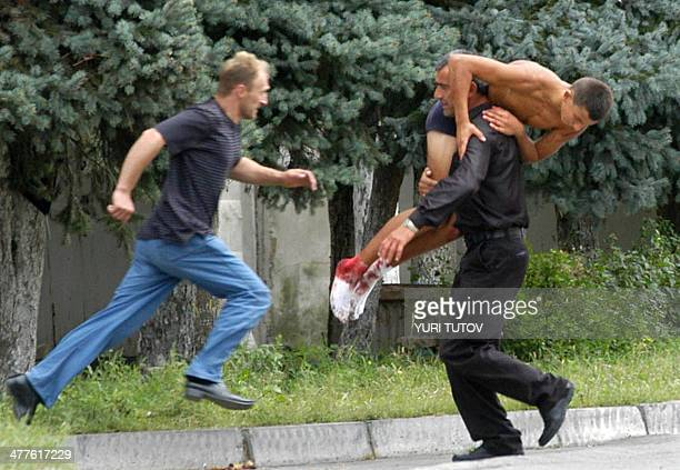 A man carries an injured schoolboy as another runs during the rescure operation in Beslan northern Ossetia 03 September 2004 One hundred and...
