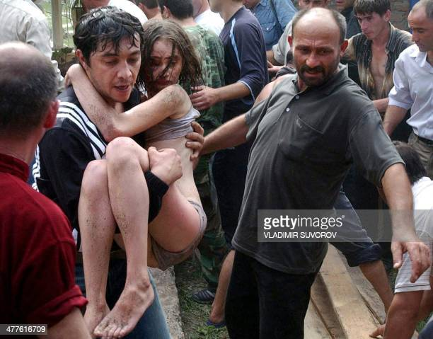 A man carries an injured schoolgirl during the rescue operation of Beslan's school northern Ossetia 03 September 2004 Dozens of corpses of dead...