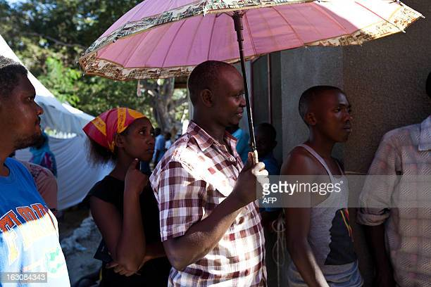 A man carries an umbrella to help with the heat during the long day of queueing in the largest polling station in Mtwapa in the Kilifi constituency...