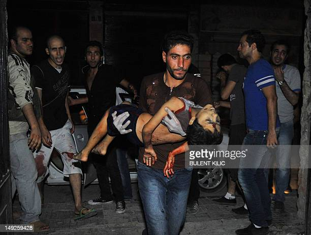 A man carries badly wounded fiveyearold Mohammed Amumrej after he was hurt during shelling by Syrian government forces in the center of Syria's...