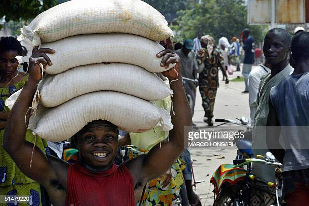 A man carries bags of flour 14 October 2004 in the central market of Kisangani President Joseph Kabila of the Democratic Republic of Congo is set to...