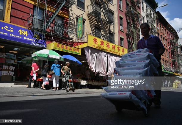 A man carries bags of rice through Chinatown on August 20 2019 in New York City With an estimated population of 90000 to 100000 people Chinatown is...