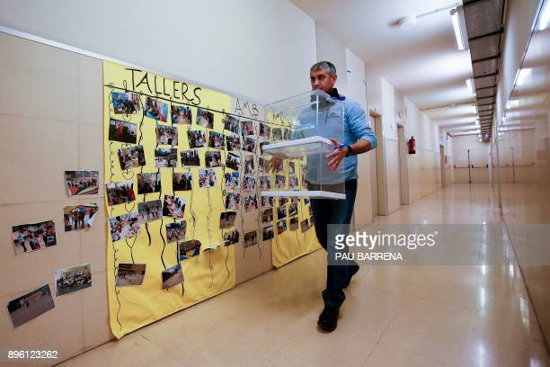 A man carries ballot boxes for the Catalan regional election during a polling station setup at the 'Prat de la Mata' school on the eve of the voting...