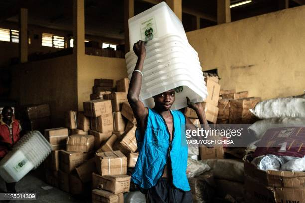 TOPSHOT A man carries ballot boxes to deliver to the polling stations at an office of the Independent National Electoral Commission in Port Harcourt...