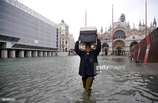 A man carries bax on his head on the flooded Piazza San Marco on November 30 2009 in Venice The acqua alta a convergence of high tides and a strong...