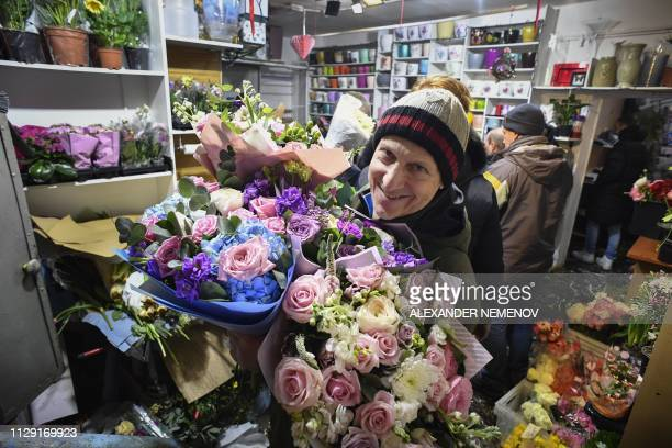A man carries bouquets of flowers as he leaves a flower shop in Moscow on March 8 on International Women's Day International Women's Day has been...