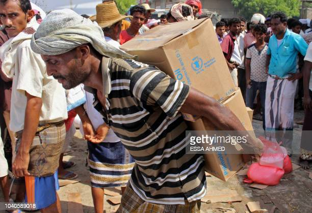 A man carries boxes containing bottles of cooking oil in the northern province of Hajjah on September 25 as Yemenis displaced from the port city of...