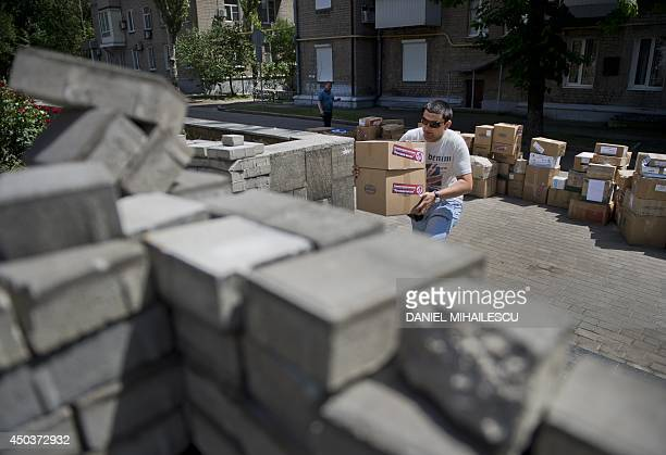 A man carries boxes containing food and medical supplies received as humanitarian help at the self proclaimed People's Republic of Donetsk's...