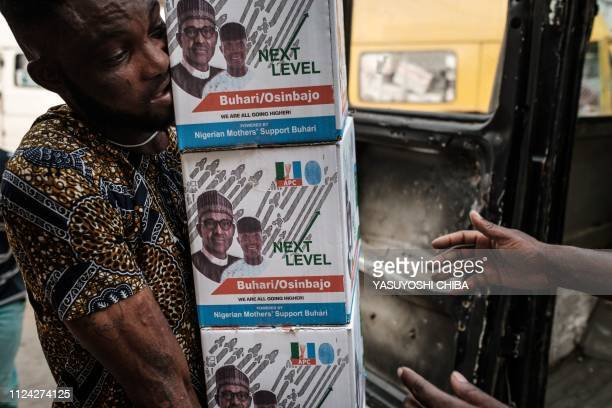 A man carries boxes of food donation with printed faces of Nigeria's incumbent President Mohammadu Buhari and Vice President Yemi Osinbajo to a van...