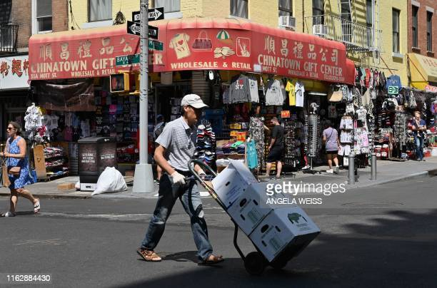 A man carries boxes through Chinatown on August 20 2019 in New York City With an estimated population of 90000 to 100000 people Chinatown is home to...