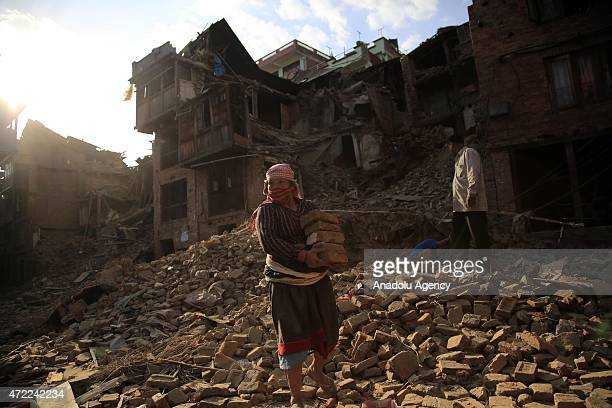 Man carries bricks near the debris of buildings in the Bhaktapur city, 20km from the capital Kathmandu, Nepal on May 5, 2015 after the devastating...