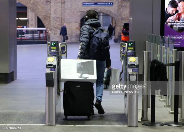 Man carries computer screens and equipment as he pulls a suitcase through the ticket barriers at King's Cross train station in central London, on...