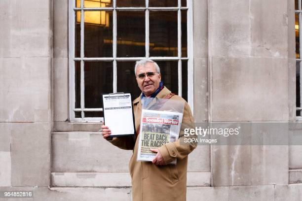 A man carries copies of the Socialist Worker publication and a signup sheet opposing the UK Independence Party of Nigel Farage ahead of an antiracism...