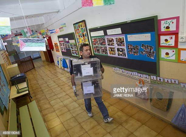 A man carries empty ballot boxes at a school in Palma de Mallorca on May 24 2014 in preparation for the European Parliament elections Some 400...