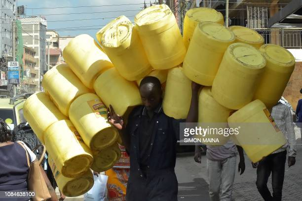 TOPSHOT A man carries empty jerry cans in the Somali neighbourhood of Eastleigh in Nairobi on January 18 2019