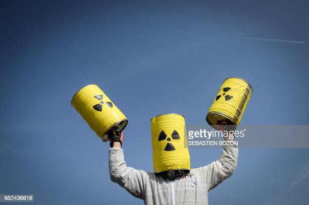 A man carries fake nuclear barrels during a demonstration to demand the closure of Fessenheim nuclear power plant on March 12 2017 in Fessenheim...