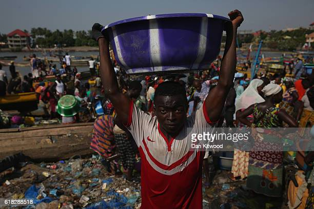 A man carries fish from boats in a fishing market on November 19 2015 in Conakry Guinea Guinea is currently counting down the necessary 42 days...