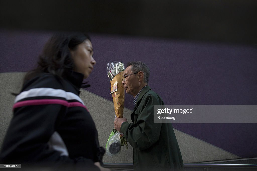 A man carries flowers near a flower market in the Mongkok district of Hong Kong, China, on Wednesday, Jan. 29, 2014. The citys financial markets will close early on Jan. 30 for the Chinese New Year holidays and resume trading on Feb. 4, while those in the mainland will be shut from tomorrow through Feb. 6. Photographer: Brent Lewin/Bloomberg via Getty Images