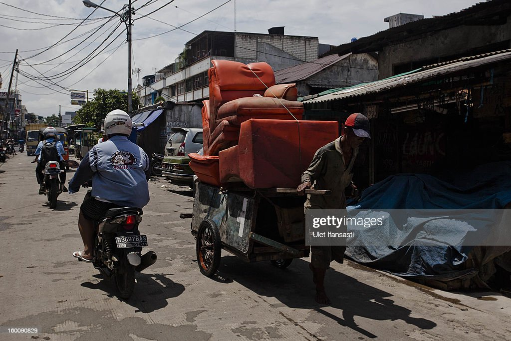 A man carries furniture by a cart as people clean up their homes after the flood in North Jakarta on January 26, 2013 in Jakarta, Indonesia. With heavy rain forecast for January 26-28, Indonesian authorities have organised the use of generators and cloud-seeding measures to defuse rain-laden clouds to help prevent further flooding of Jakarta, following last week's floods which claimed the lives of 32 people.