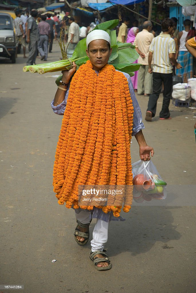 A man carries garlands of marigolds, fresh fruits and small banana tree stalks to decorate a business in Central Calcutta in honor of Diwali. During Diwali, the five-day Indian festival of lights, homes are thoroughly cleaned and windows and doors are opened to welcome Laksmi, the goddess of wealth. Mythically, the festival celebrates the victory of the Hindu god Lord Rama over the demon Ravana, and Rama's return to the holy city of Ayodhya..