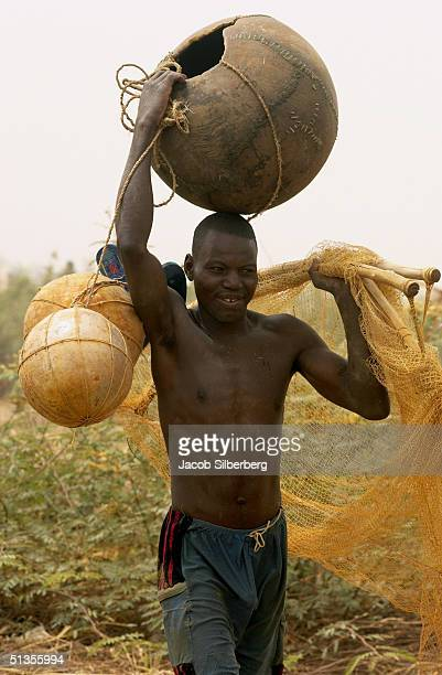 A man carries gourds used to help him float in the water and store the fish he caught during the Argungu Fishing Festival on March 19 2004 in Argungu...