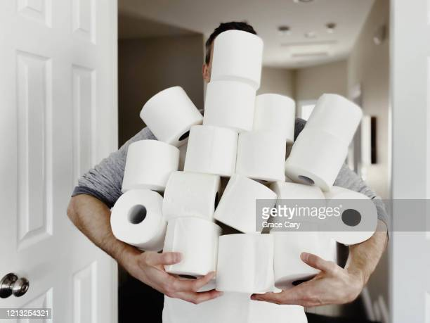 man carries heap of toilet paper - panic buying stock pictures, royalty-free photos & images