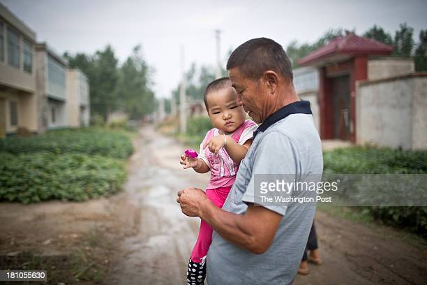 A man carries hhis grand daugther down a street at a rural village near Fuyang Anhui Province China on 28 August 2013 As ablebodied adults seek work...