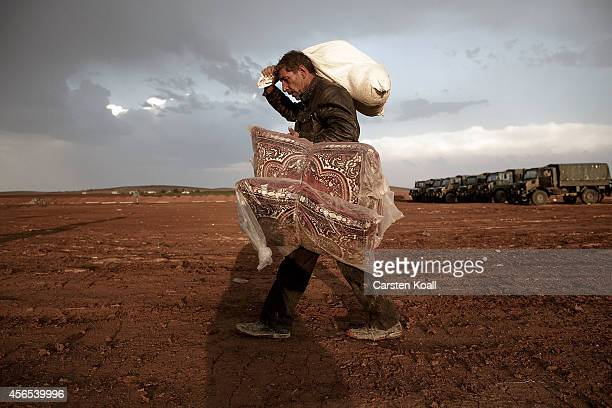 A man carries his belongings after he had arrived from Syria at the border crossing on October 2 2014 near Suruc Turkey The Turkish Parliament is...