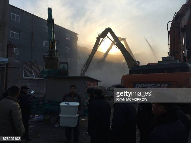 A man carries his belongings as demolition works take place at the site of a fatal housing block fire in Beijing on November 19 2017 Chinese...
