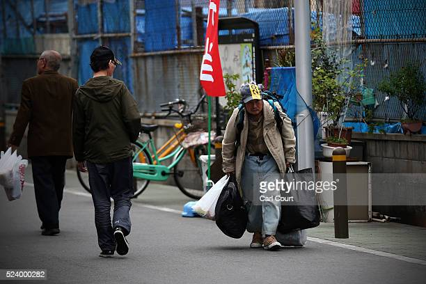 A man carries his belongings in the slum area of Kamagasaki on April 23 2016 in Osaka Japan Kamagasaki a district in Japan's second largest city...
