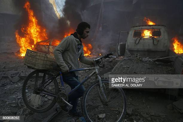 A man carries his bicycle past debris and burning cars following reported airstrikes in the town of Hamouria in the eastern Ghouta region a rebel...