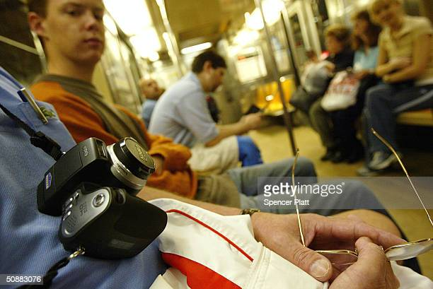 A man carries his camera on a New York City subway May 21 2004 in New York City Citing security concerns New York City Transit has proposed a ban on...