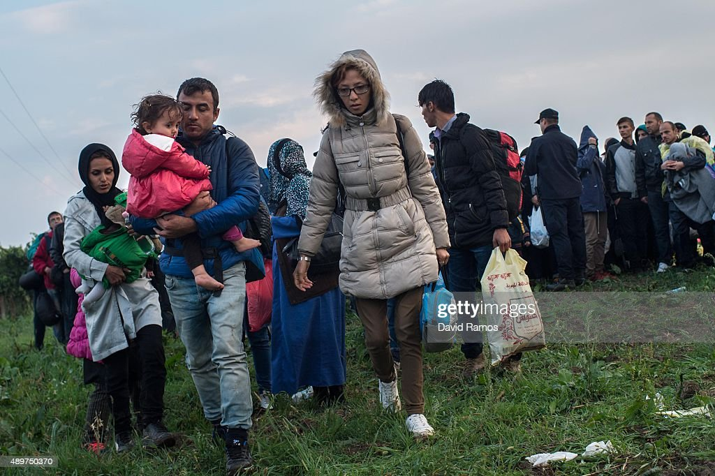 A man carries his child as he and other migrants make their way to board buses heading to a refugee transit camp after crossing into Croatia through the Serbian border on September 24, 2015 in Bapska, Croatia. More than 40,000 migrants have crossed into Croatia from Serbia since Tuesday last week. Croatia said yesterday it can not cope with this increasing number of migrants crossing its border and that Serbia should bus them also to Hungary and Romania. European Union ministers agreed Tuesday to relocate 120,000 refugees among country members to ease the migration pressure on nations like Greece and Italy.