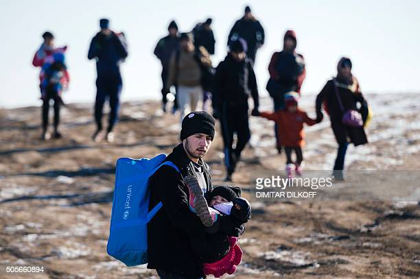 A man carries his child as they walk with other migrants and refugees after crossing the Macedonian border into Serbia near the village of Miratovac...
