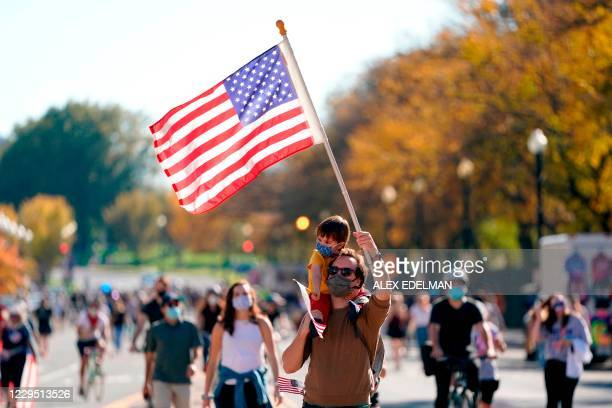 Man carries his child as they wave US flags while celebrating on Black Lives Matter plaza across from the White House in Washington, DC on November 7...