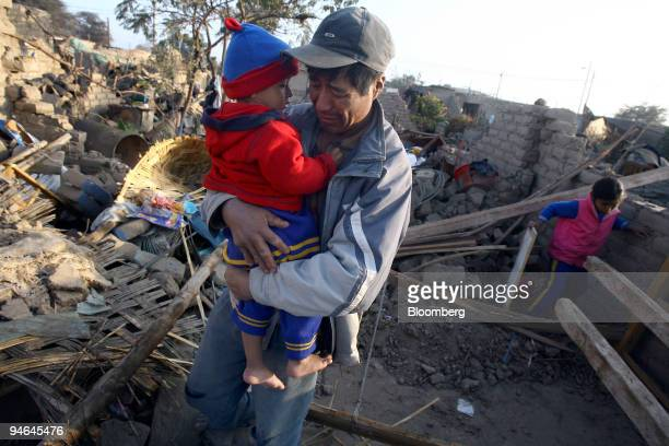 A man carries his child near the remains of their house in the town of Pisco Peru on Thursday Aug 16 2007 The death toll from Peru's worst earthquake...