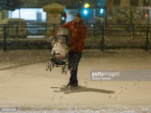 A man carries his child on a pushchair in a street covered by snow during a heavy snowfall in Burgos northern Spain on February 28 2018 School was...