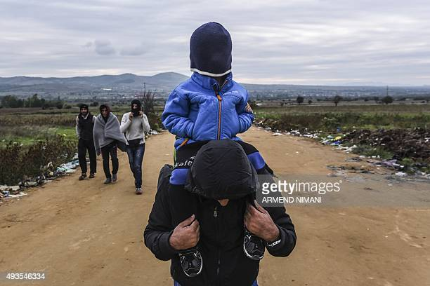 A man carries his child on his shoulders as they walk on a dirt road with other migrants and asylum seekers after crossing the MacedonianSerbian...