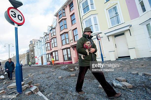 A man carries his dog over debris on Aberystwyth promenade on January 7 2014 in Aberystwyth United Kingdom A major cleanup operation has started...
