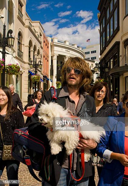 A man carries his dog while shopping on Rodeo Drive on April 14 2012 in Beverly Hills California Millions of tourists flock to the Los Angeles area...
