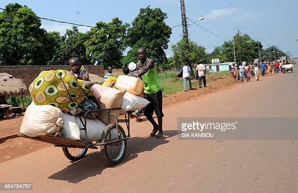 A man carries his luggages and his child on a cart through a checkpoint held by French soldiers of the Sangaris operation on December 10 2013 in the...