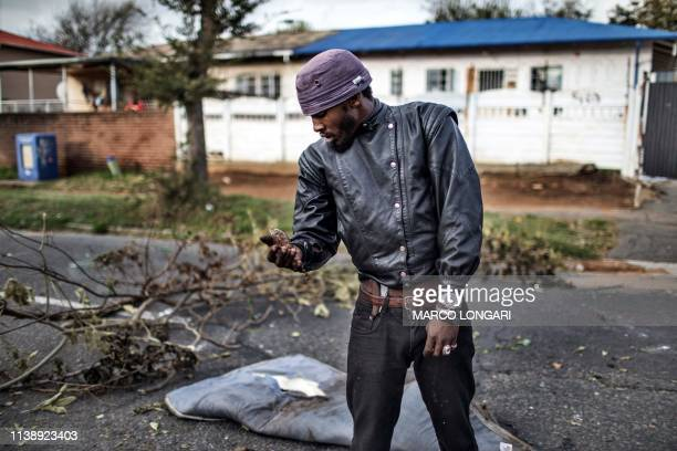 TOPSHOT A man carries his pet a salamander called Rokkie in Johannesburg on April 23 2019 during a protest against the lack of service delivery or...