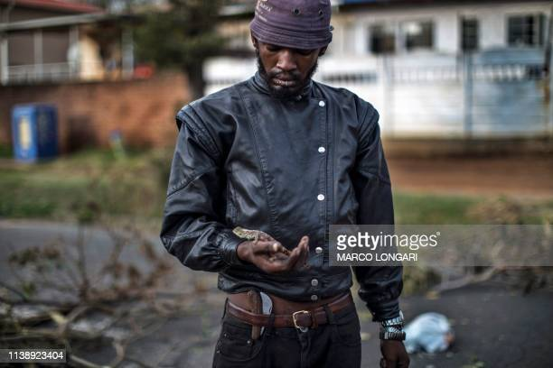 A man carries his pet a salamander called Rokkie in Johannesburg on April 23 2019 during a protest against the lack of service delivery or basic...